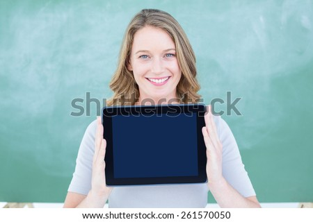 Smiling teacher holding tablet pc in front of blackboard in classroom - stock photo