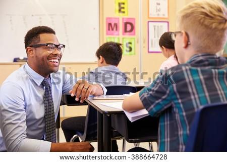 Smiling teacher kneeling beside elementary school pupilâ??s desk - stock photo