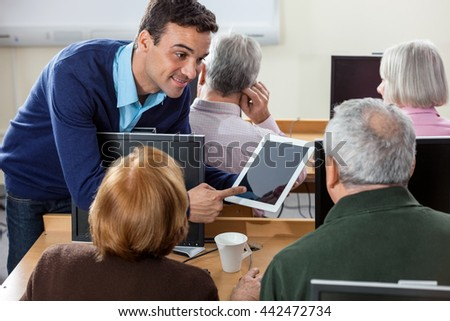 Smiling Teacher Showing Digital Tablet To Senior Students In Cla - stock photo