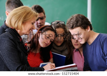 Smiling teacher standing in a classroom showing a book to her students - stock photo