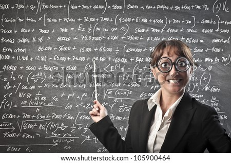 Smiling teacher wearing thick eyeglasses and showing a blackboard - stock photo