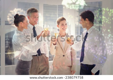 Smiling team of business people clinking their flutes of champagne against colourful fireworks exploding on black background