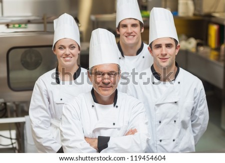 Smiling team of Chef's standing in kitchen