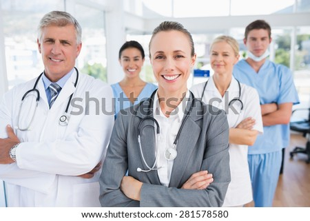 Smiling team of doctors looking at camera in medical office - stock photo