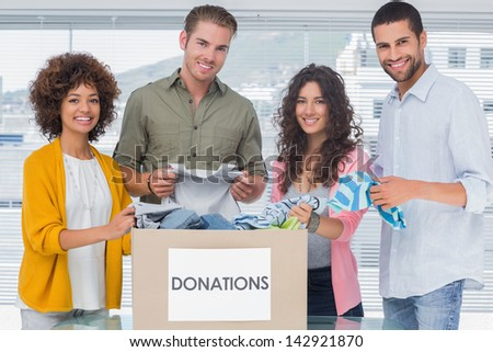 Smiling team of volunteers taking out clothes from a donation box for a charity - stock photo