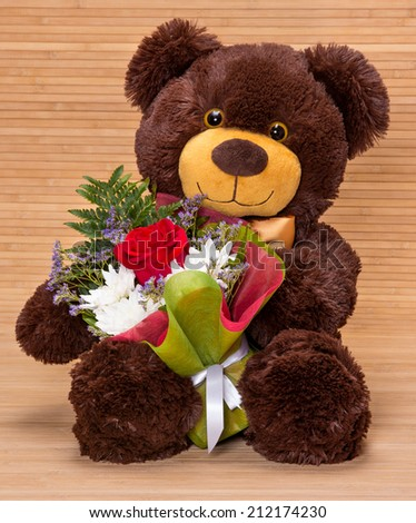 Smiling teddy bear holding beautiful floral bouquet in paws - stock photo