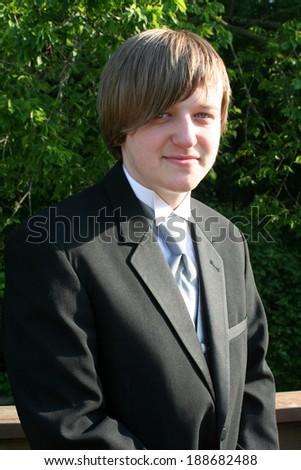 Smiling Teen Boy In Black Tuxedo Vertical - stock photo