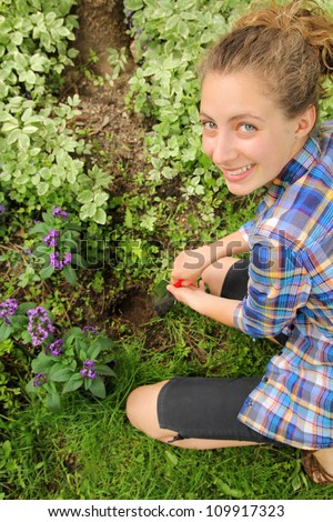 Smiling teen doing a hole for the purple flowers