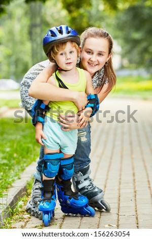 Smiling teen girl and little boy in roller protective equipment stand embraced on walkway in park - stock photo