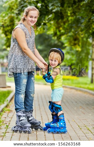 Smiling teen girl and little boy in roller protective equipment stand holding hands on walkway in park - stock photo