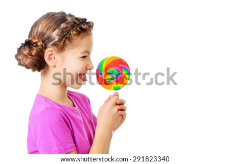 Smiling teen girl enjoys her huge lollipop. Studio shot. Isolated over white. - stock photo