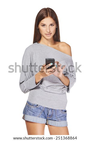 Smiling teen girl text messaging on her mobile, isolated over white - stock photo