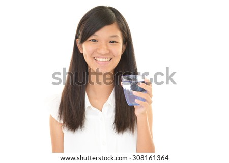 Smiling teen girl with glass of water