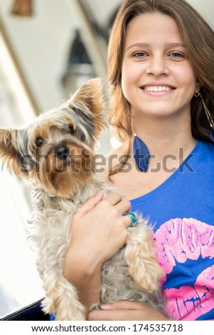 Smiling teen girl with her little  dog