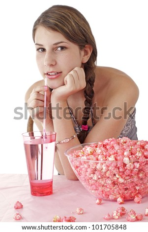Smiling teen girl with long brown braids sips drink through a straw. Large bowl of pink popcorn and tall glass are on table in foreground. Vertical, isolated on white with copy space.