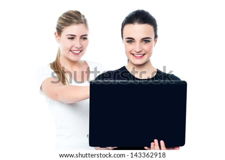 Smiling teen girls watching funny videos on laptop.