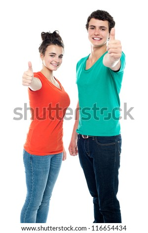 Smiling teen love couple showing thumbs up to camera together - stock photo