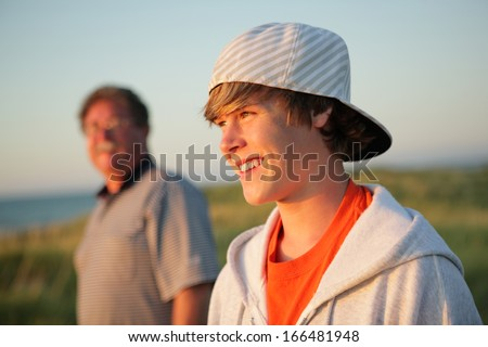 Smiling teen with father - stock photo