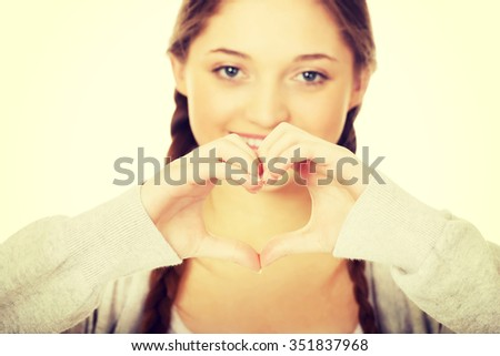 Smiling teen woman making heart shape with her hands. - stock photo