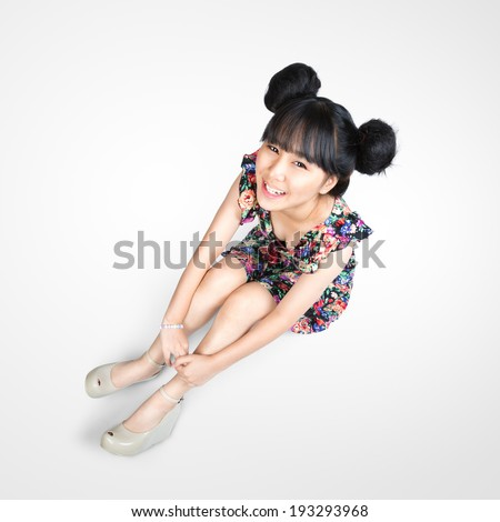 Smiling teenage asian girl sitting on the floor. - stock photo