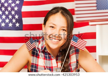 Smiling teenage Asian girl with flags of USA