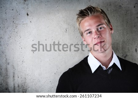 Smiling teenage boy against a cement wall - stock photo
