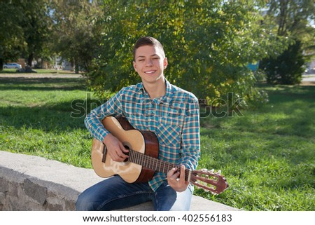 smiling teenage boy and guitar on outdoor in spring