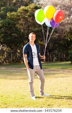smiling teenage boy holding bunch of colorful helium balloons - stock photo
