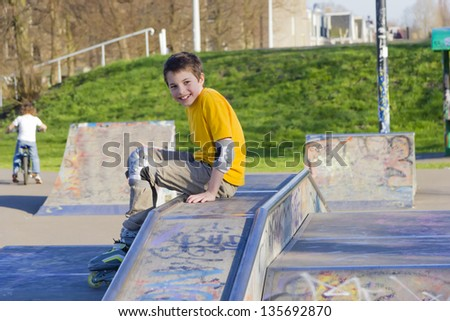 smiling teenage boy in roller-blading protection kit in a skate park - stock photo