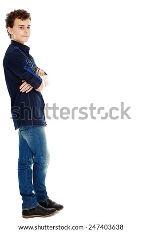 Smiling teenage boy with arms crossed leaning against the side of the image - stock photo