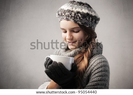 Smiling teenage gild in warm clothes holding a bowl of hot drink - stock photo