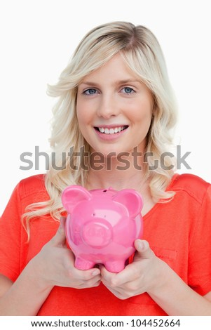 Smiling teenage girl holding a pink piggy bank against a white background - stock photo