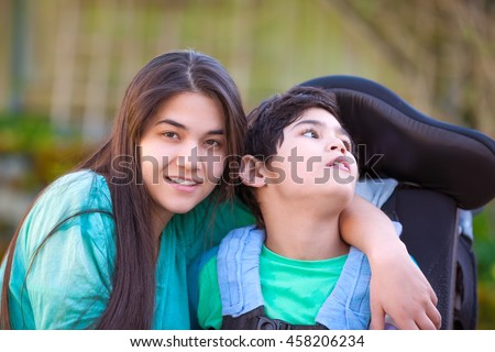 Smiling teenage girl hugging disabled nine year old brother in wheelchair outdoors - stock photo