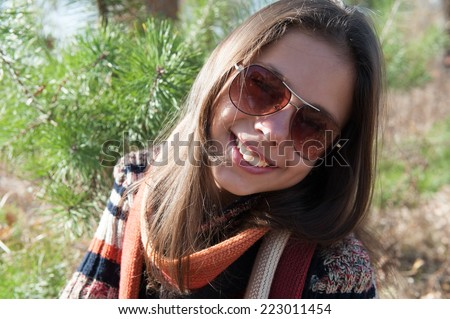 Smiling teenage girl in sunglasses. Autumn in the park