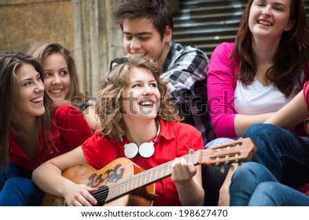 Smiling teenage girl playing guitar for her friends - stock photo