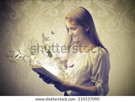Smiling teenage girl reading a book with birds coming out from it - stock photo