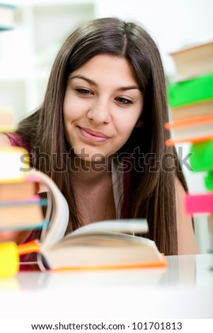 Smiling Teenage girl reading her book for school