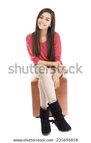 Smiling teenage girl sitting and looking at camera against white background - stock photo