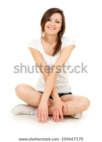 smiling teenage girl sitting on the floor with crossed legs, full length, white background - stock photo