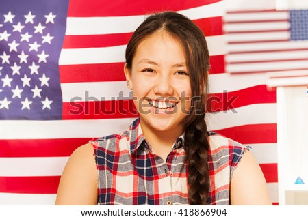 Smiling teenage girl with American flag behind her