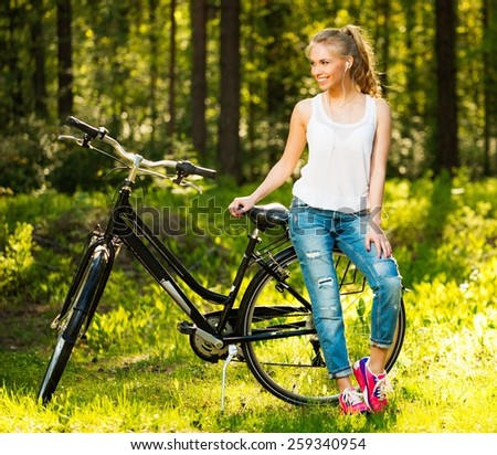 Smiling teenage girl with bicycle in a park on sunny day - stock photo