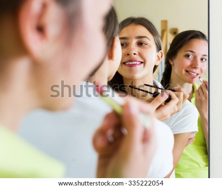 Smiling teenage girlfriends having fun while putting make up in front of a mirror  - stock photo