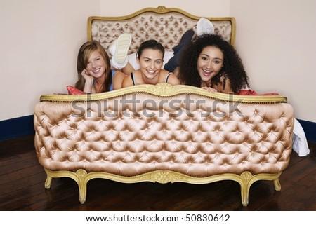 Smiling Teenage Girls lying on funky cushion bed - stock photo