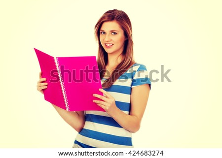 Smiling teenage woman reading her notes - stock photo