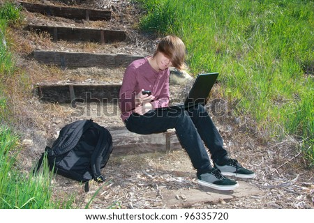 Smiling teenaged boy sitting on outdoor steps with laptop on lap, phone in hand and backpack nearby. - stock photo