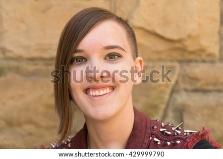 Smiling teenaged girl with punk haircut.