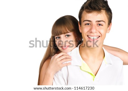 Smiling teenager boy with his beautiful girlfriend on his back isolated over white - stock photo