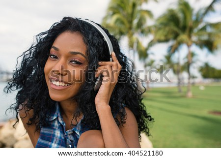 Smiling teenager close up portrait with headphones listening to music in South Pointe Park. South Beach Miami, Florida. - stock photo