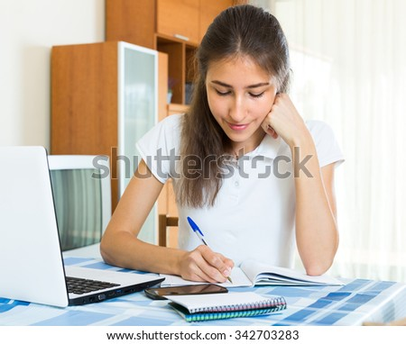 Smiling teenager girl doing homework at the table at home