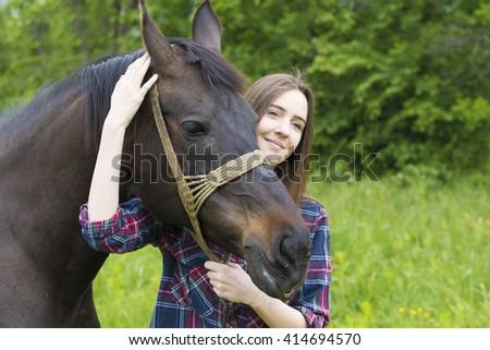Smiling teenager girl hugs her horse pet - stock photo
